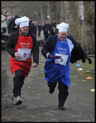 Total Politics editor Ben Duckworth (left) and Lord Rennard take part in the MP's and Lords race against political Journalist in the Rehab Parliamentary Pancake Shrove Tuesday race a charity event which sees MPs and Lords joined by media types in a race to the finish. Victoria Tower Gardens, Westminster, Tuesday February 12, 2013. Photo By Andrew Parsons / i-Images<br />