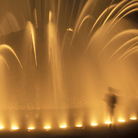 USA, Washington, Seattle, Visitors stand in spray of International Fountain at Seattle Center park on summer night