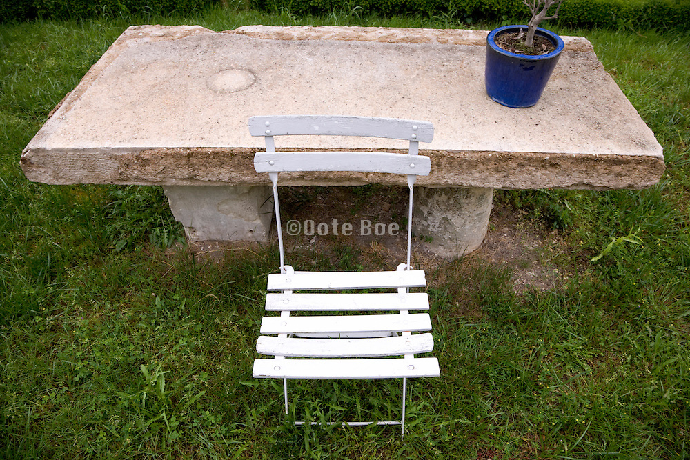 stone table with garden folding chair and plant pot
