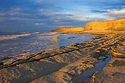 Kilve Beach on the North Somerset Coast in the late evening. The low angle of the sun allowed the light ot reflect off the top of the waves and the clifs making the waves seem to glow.<br /> Kilve Beach is a Site of Special Scientific Interest (SSSI) because of the fossils and geology.