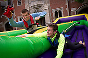 Competitors reach to place a velcro beanbag as far as possible before their elastic harnesses pull them back during Grinnell Relays on Mac Field. BEN BREWER/Grinnell College