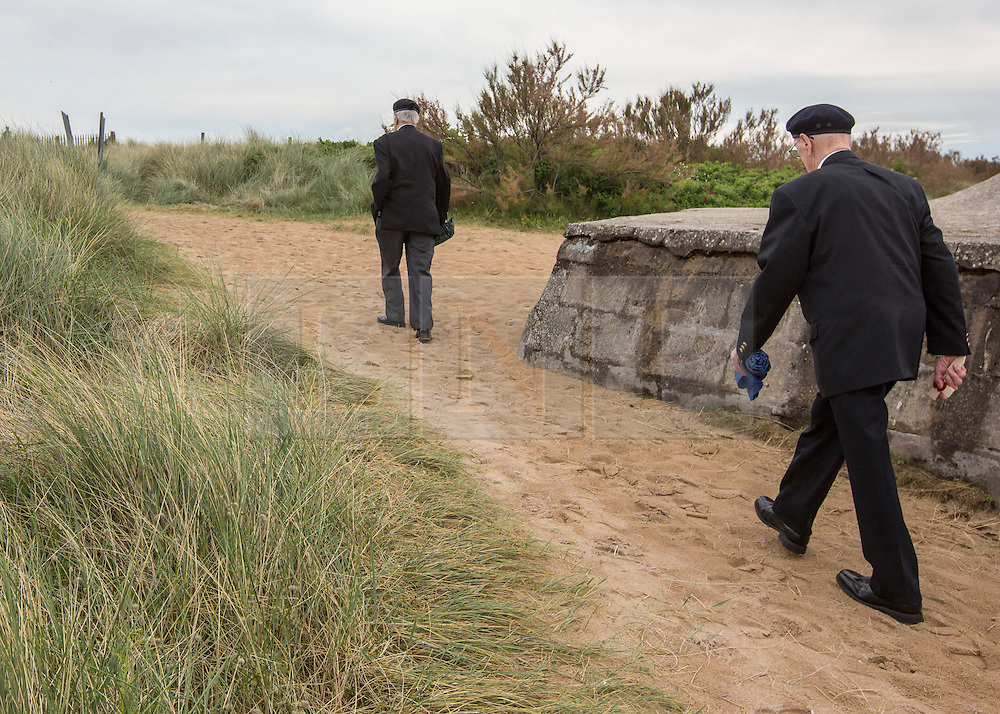 © Licensed to London News Pictures. 29/05/2014. Arnie Salter and David Roberts walk onto Juno beach as they pay their respects to the members of the Royal Navy who served alongside them. . Photo credit : Alison Baskerville/LNP
