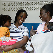 Reine Zenae (32, at left) was immunized against tetaunus before the birth of her son, Siatizi (pictured in the arms of midwife Marie-France Die), greatly reducing the risk of Maternal and Newborn Tetanus (MNT), which is a major cause of child mortality in Cote d'Ivoire. Reine is holding two year-old Ariel, a neigbour's daughter. Zouan, western Cote d'Ivoire, 13 August 2012.