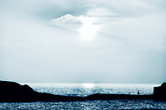 Silhouette of a fisherman walking on a rock at the sea at sunset.