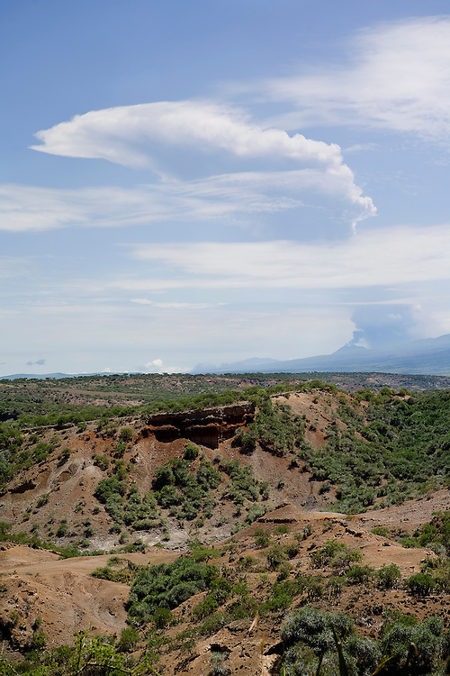 Reminiscent of the geological history of Olduvai Gorge since prehistoric times, Ol Doinyo Lengai sends an ash plume high into the atmosphere. Millions of years ago, Olduvai was a large lake, and its shores were covered with successive deposits of volcanic ash. Olduvai Gorge, Tanzania.