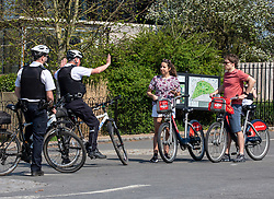 © Licensed to London News Pictures. 11/04/2020. London, UK. Two Police cyclists patrolling Richmond Park question two cyclist where a cycling ban is in place for adults in the park during the coronavirus disease pandemic. Londoners have been told to stay at home and only leave homes to exercise or when absolutely essential in an attempt to fight the spread of COVID-19 as temperatures for the Easter Bank holiday weekend are expected to reach 26c. Photo credit: Alex Lentati/LNP