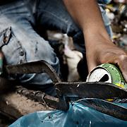 """Extracción del aluminio de las latas de refresco en un taller de Mokattam . En medio del barrio de Manshiet Nasr a las afueras de El Cairo esta situado el asentamiento de Mokattam conocido como la """"Ciudad de la Basura"""" , está habitado por los Zabbaleen ,una comunidad de unos 45.000 cristianos coptos que viven desde hace varias décadas de reciclar los desperdicios que genera la capital egipcia: plástico, aluminio, papel y desechos órganicos que transforman en compost . La mayoría forman parte de la Asociación para la Protección del Ambiente (APE) una ONG que actúa en el área, cuyos objetivos son proteger el medio ambiente y aumentar el sustento de las recuperadores de basura de El Cairo. Según la ONU, el trabajo que se realiza en Mokattam como uno de los diez mejores ejemplos del mundo en el mejoramiento medioambiental. El Cairo , Egipto, Junio 2011. ( Foto : Jordi Camí )"""