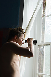 Shirtless man looking with binoculars out a window