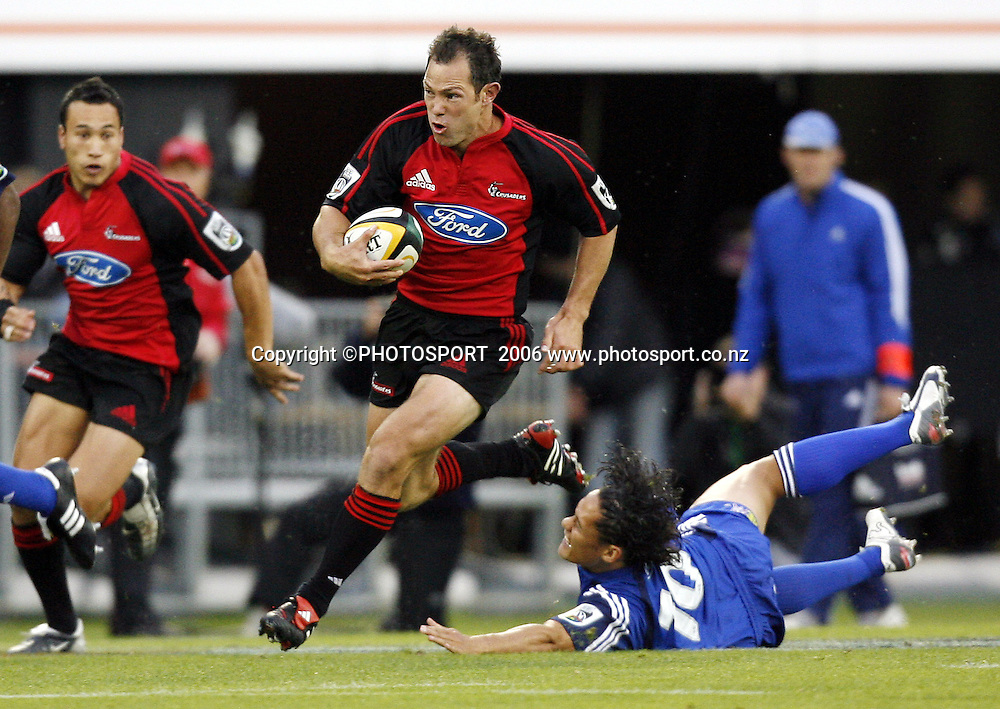 Leon MacDonald beats the tackle of Tasesa Lavea during the 2006 Super 14 Rugby Union match between the Crusaders and the Blues at Jade Stadium, Christchurch, on Saturday 4 March 2006. Photo: Anthony Phelps/PHOTOSPORT