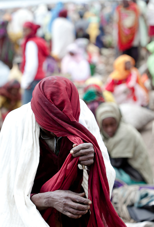 A muslim man puts on his turban in Dinsho market in the Bale Mountains of Ethiopia