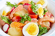 Closeup of bowl with salad of mixed ingredients: boiled potatoes and eggs, smoked salmon, cherry tomatoes, lettuce and red radish.