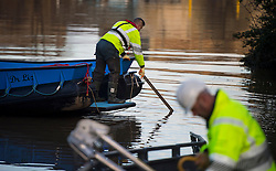 © Licensed to London News Pictures. 29/12/2015. York, UK. A member of the environment agency tests the depth of the water near the Foss Barrier while it is closed in York city centre. Several warnings of risk to life are sill in place in parts of Lancashire and Yorkshire where rainfall has been unusually high, causing heavy flooding. Photo credit: Ben Cawthra/LNP