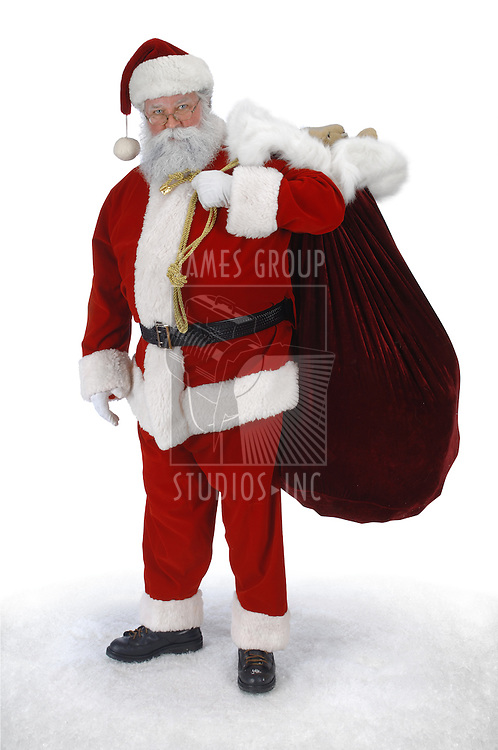 Full length Santa standing in snow with sack of toys on a white background