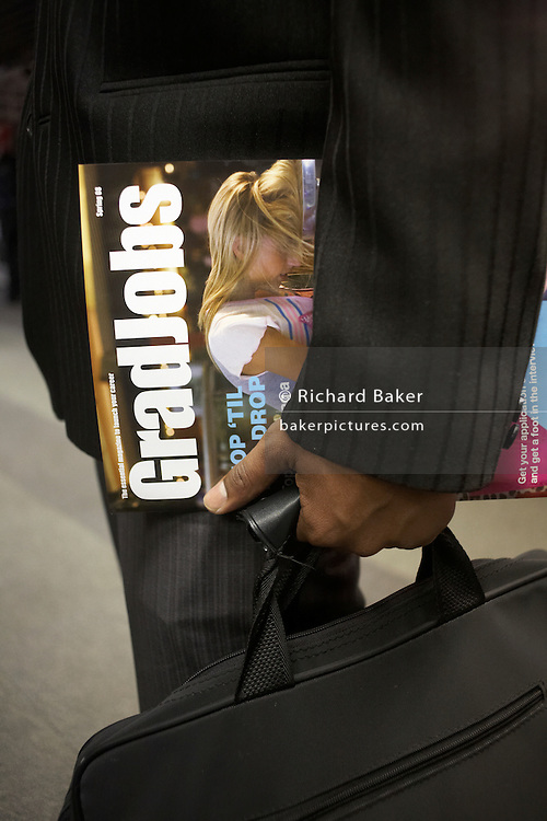 Detail of a hand holding a job magazine at a graduate expo fair where company job recruiters meet young people starting work