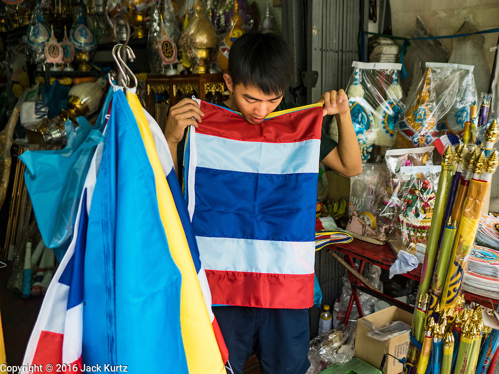 10 AUGUST 2016 - BANGKOK, THAILAND: A vendor folds up a Thai flag her sold to a man buying supplies for the Queen's Birthday. Thais are preparing for the Queen's birthday. Queen Sirikit of Thailand, was born Mom Rajawongse Sirikit Kitiyakara on 12 August 1932. She married  Bhumibol Adulyadej, King of Thailand (Rama IX) in 1950. He is the longest serving monarch in the world and she is longest serving consort of a monarch. Her birthday, like the King's Birthday (which falls on Dec. 5),  is a national holiday in Thailand. Her birthday, August 12, is also celebrated as Mothers' Day in Thailand. Thais hang portraits of Queen Sirikit in their homes and fly her royal flag on her birthday.        PHOTO BY JACK KURTZ