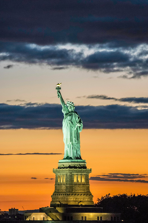 The Statue of Liberty rises against the Summer sunset sky in New York City.