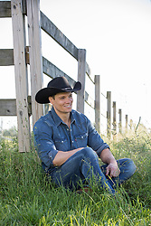 hot cowboy sitting in a field by a rustic fence
