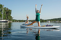 Lori Card and Abbie Roy get acclimated with their balance with side lunges during EKAL's SUP Yoga classes on Meredith Bay Wednesday morning.   (Karen Bobotas/for the Laconia Daily Sun)