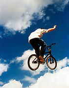 BMX rider releasin his hand from the handle bars while in mid air, UK 2000's