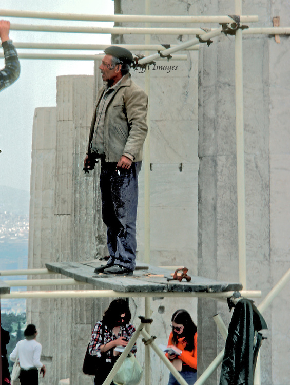 Two young women tourists study their guidebooks while above them a workman stands on a scaffold platform, smoking a cigarette, while talking with another workman installing the scaffolding, his bent arm just visible.
