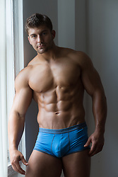 muscular man in tight underwear at home by a window