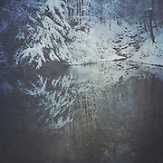 Pond reflecting snow covered trees - texturized photograph, processed on iPhone