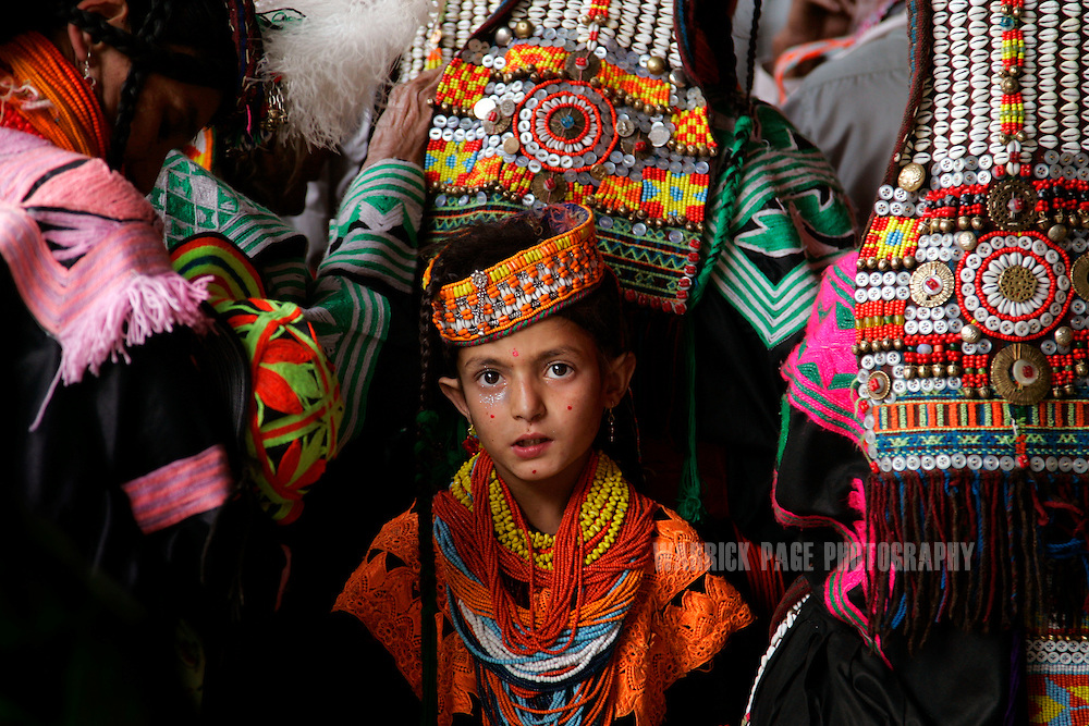 "KALASHA VALLEYS, PAKISTAN - MAY 15: A Kalash girl stands amongst women praying and telling historical stories during the ""Joshi"" (spring) festival in the village of Batrik May 15, 2008 in the Kalasha Valleys, northwestern Pakistan. The Joshi Festival is a celebration of dance, music and prayer to welcome the coming of warmer season and the new life and crops it brings. The shrinking Kalash community of 4000, who claim to be descendants of Alexander the Great and worship several gods, are considered by many Pakistanis to be unclean, lazy and heretics. They often face ridicule and persecution for their polytheistic religion and fear the spread of hard-line Islamism bordering their communities. (Photo by Warrick Page)"