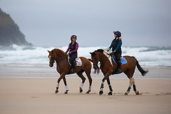© Licensed to London News Pictures. 04/07/2020. Perranporth, UK. Emily Dunstan (L) and Tina Wallace (R) ride horses along Perranporth beach in Cornwall today, despite wet weather. Today marks a lift in COVID-19 restrictions, as pubs are allowed to open, whilst customers must still follow social distancing guidelines. Tens of thousands of tourists are due to arrive in Cornwall over this weekend, as overnight stays within England are also allowed. Photo credit : Tom Nicholson/LNP