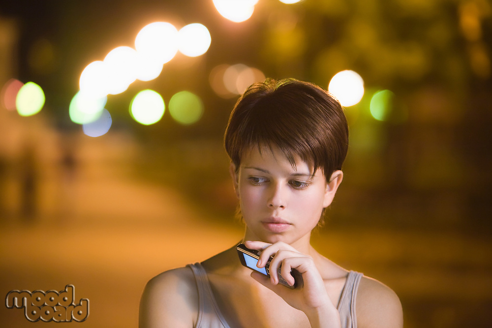 Teenage girl stands thinking with mobile phone in street
