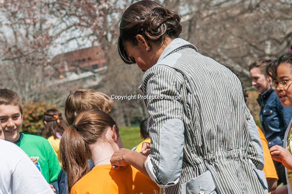 (L) Rachel Bradley, of Sarah Moore Greene Magnet Technology Academy School, Knox County, TN  gets her shirt signed by First Lady Michelle Obama during an event where she with fellow classmate  and the First Lady planted the White House Kitchen Garden for the fifth year in a row at the White House on April 4, 2013 in Washington DC. Photo by Kris Connor