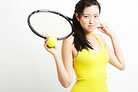 Portrait of young Asian female tennis player holding racket and ball against white background
