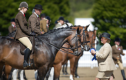 © Licensed to London News Pictures. 10/05/2017. Windsor, UK. Judge Miss M L Hennessy carries a rosette for a winner in the Small Hunter competition category on the first day of the Royal Windsor Horse Show. The five day equestrian event takes place in the grounds of Windsor Castle. Photo credit: Peter Macdiarmid/LNP