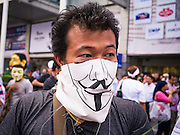"09 JUNE 2013 - BANGKOK, THAILAND:  A member with a Guy Fawkes mask at an anti-government protest on the plaza in front of Central World in Bangkok. The White Mask protesters wear the Guy Fawkes mask popularized by the movie ""V for Vendetta"" and the protest groups Anonymous and Occupy. Several hundred members of the White Mask movement gathered on the plaza in front of Central World, a large shopping complex at the Ratchaprasong Intersection in Bangkok, to protest against the government of Thai Prime Minister Yingluck Shinawatra. They say that her government is corrupt and is a ""puppet"" of ousted (and exiled) former PM Thaksin Shinawatra. Thaksin is Yingluck's brother. She was elected in 2011 when her brother endorsed her.    PHOTO BY JACK KURTZ"