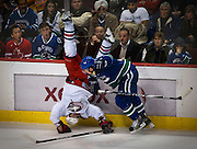 Columbus Blue Jackets Jakub Voracek is upended by Vancouver Canucks Dan Hamhuis during NHL hockey in Vancouver, BC. (2011)