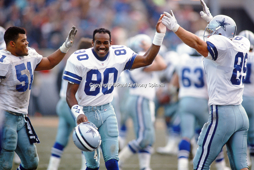 Dallas Cowboys linebacker Ken Norton, Jr. (51), Dallas Cowboys wide receiver Alvin Harper (80), and Dallas Cowboys tight end Rob Awalt (89), raise their arms in celebration during the NFL NFC Wild Card playoff football game against the Chicago Bears on Dec. 29, 1991 in Chicago. The Cowboys won the game 17-13. (©Paul Anthony Spinelli)