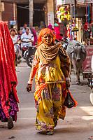 An Indian woman walking down a street in Jaisalmer, Rajasthan, India.