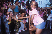 A young black child dancing, while a crowd of people look on cheering, Notting Hill Carnival, London, UK 2004