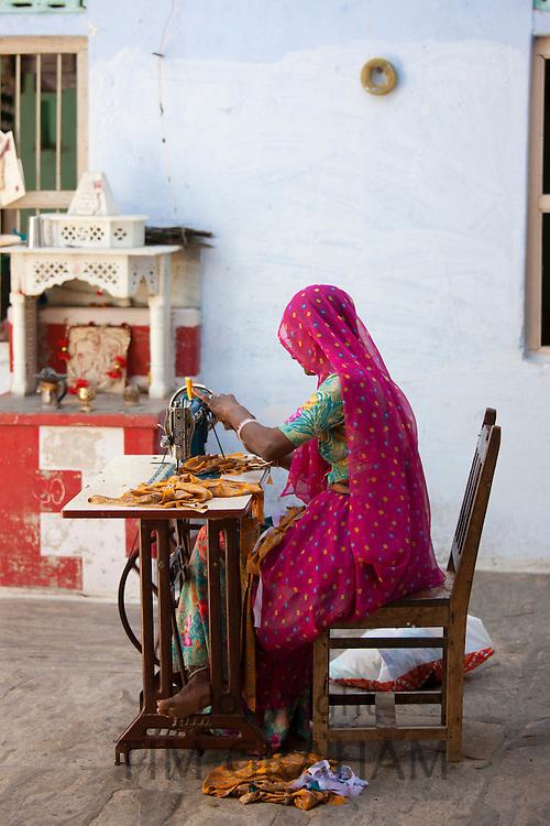 Indian woman in Rajasthani sari works at home using sewing machine in Nimaj village, Rajasthan, India