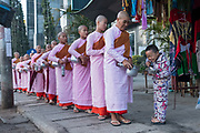 Nuns in procession from Padonmar Sari Nunnery collecting offerings on the streets of Taunggyi, Myanmar
