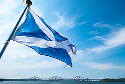 Scottish saltire flag flying from rear of ship on Firth of Forth river in Scotland, UK, United Kingdom