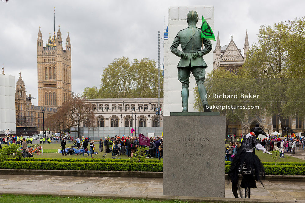 On the 10th consecutive day of protests around London by the climate change campaign Extinction Rebellion, a protester on stilts prepares to strut across Parliamant Square, on 24th April 2019, in Westminster, London England.