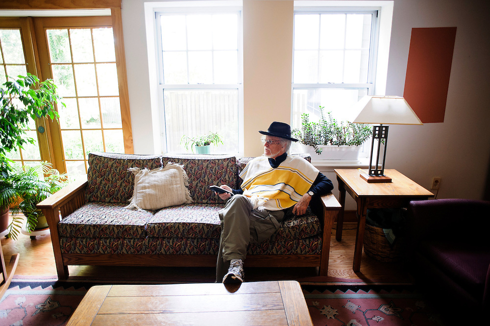 photo by Matt Roth..Takoma Village Cohousing resident James McDonough sits in the Common House's living room, Saturday, September 22, 2012, looking for the Michigan vs. Notre Dame football game, but struggles with the cable's intricate menu system.