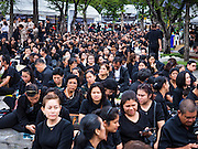 29 OCTOBER 2016 - BANGKOK, THAILAND:  Mourners line up on Sanam Luang and wait to go into the Grand Palace to pay homage to the late King. Saturday was the first day Thais could pay homage to the funeral urn of the late Bhumibol Adulyadej, King of Thailand, at Dusit Maha Prasart Throne Hall in the Grand Palace. The Palace said 10,000 people per day would be issued free tickerts to enter the Throne Hall but by late Saturday morning more than 100,000 people were in line and the palace scrapped plans to require mourners to get the free tickets. Traditionally, Thai Kings lay in state in their urns, but King Bhumibol Adulyadej is breaking with tradition. His urn reportedly contains some of his hair, but the King is in a coffin,  not in the urn. The laying in state will continue until at least January 2017 but may be extended.      PHOTO BY JACK KURTZ