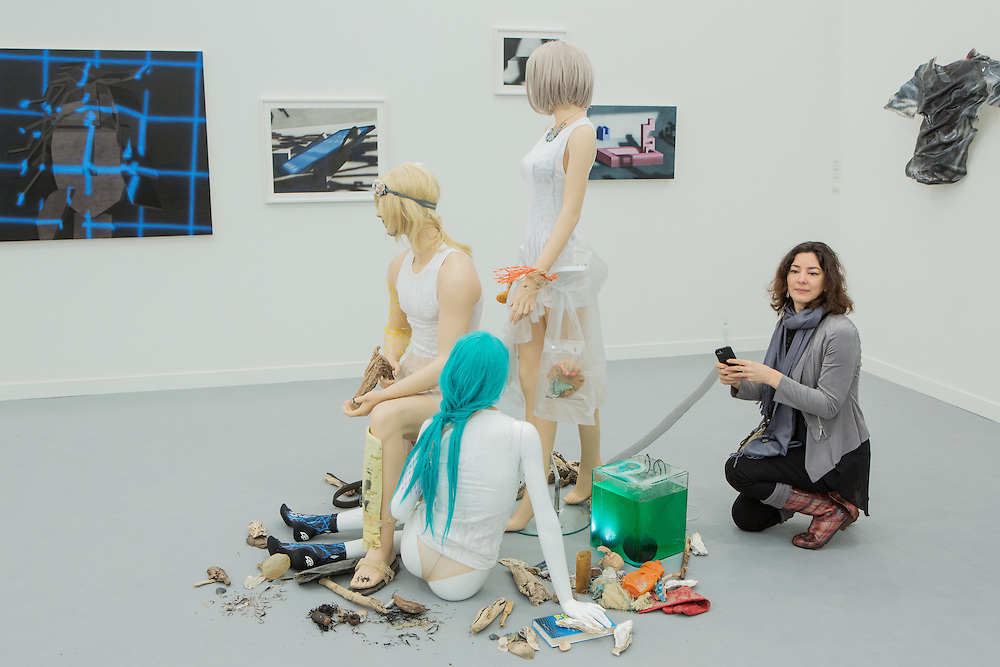 """New York, NY - 6 May 2016. Frieze New York art fair. A woman taking a photo of """"Seastead Figures (Polypool)"""", by David Keller and Ella Plevin in the gallery of Kraupa-Tuskany Zeidler of Berlin."""