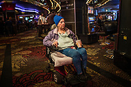 Woman uses an electric scooter to move around a casino on the old strip, Fremont Street, Las Vegas.  Nevada.
