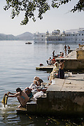 Women do laundry washing and men bathe at the ghats by Lake Pichola, Udaipur, India