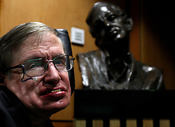 Professor Stephen Hawking poses in front of a bust of himself, which was unveiled tonight in Cambridge University's new Centre for Theoretical Cosmology.