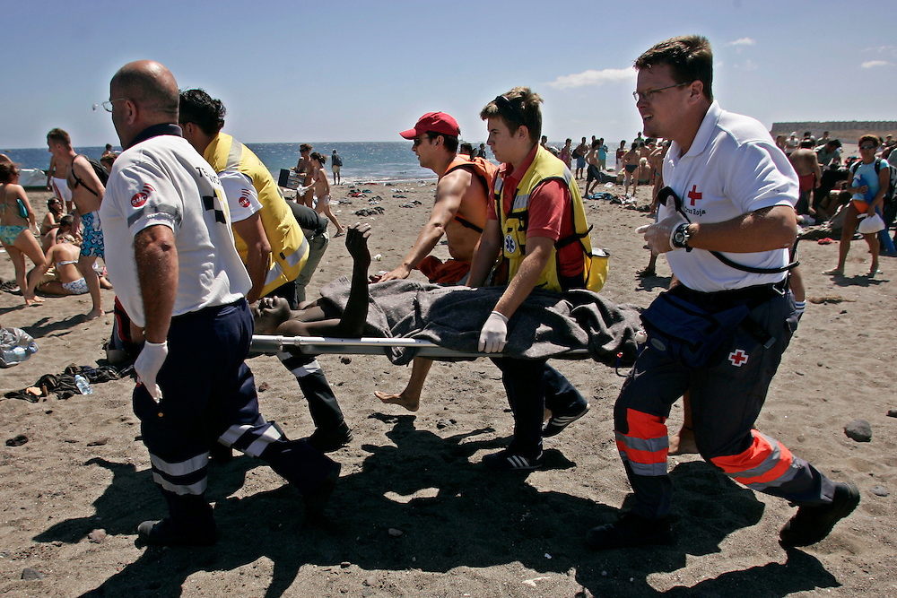 An immigrant is carried on a stretcher accross a tourist beach after a small boat of would-be immigrants landed on the Tejita beach in Granadilla on the Canary island of Tenerife, Spain, Sunday, July 30, 2006. More than 117 would-be immigrants arrived in different boats Sunday in Tenerife, two of whom were found dead. More than 11,000 Africans from some of the continent's poorest countries have made the perilous trip to the Canary Islands from western coasts so far this year, already doubling the total for all of 2005. More than 1,000 are reported to have died attempting the voyage since late last year.