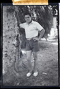male person posing by tree in front of house 1950s