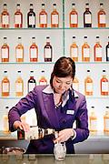 "Yamazaki, November 22 2011 - Suntory whisky distillery in Yamazaki, Japan. A waitres preparing "" High Ball "", a popular way to drink whisky and soda in Japan."
